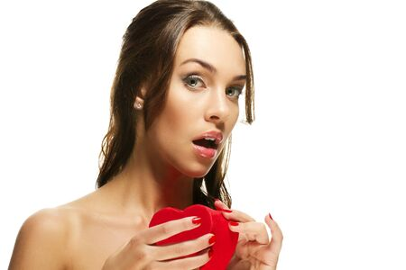 beautiful woman about to open a red heart shaped box on white background photo