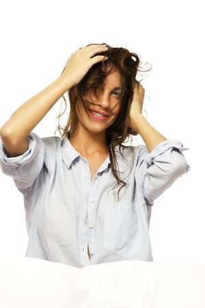 happy woman in pajamas playing with her hair on white background Stock Photo - 11975498