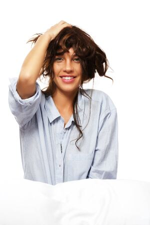 happy woman in pajamas playing with her hair on white background photo