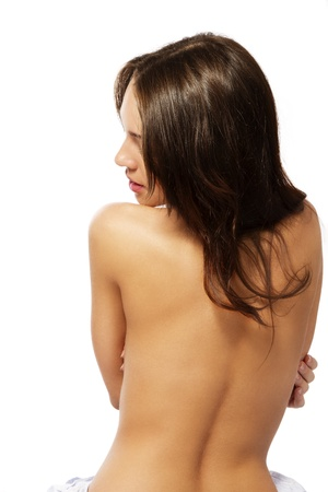 nude girl sitting: naked back of a beautiful brunette woman on white background