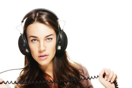beautiful woman with headphones holding cord on white background photo