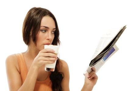 beautiful woman drinking latte macchiato coffee reading newspaper on white background photo