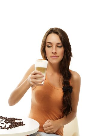 latte macchiato: beautiful woman sitting on a table looking at the latte macchiato coffee in her hand on white background Stock Photo