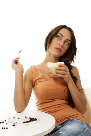 dreaming woman with cappuccino coffee sitting at a table on white background photo