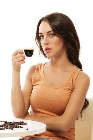 elegant young woman sitting at a table with espresso coffee on white background photo