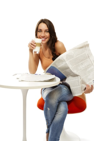 hot news: happy young woman with latte macchiato coffee and a newspaper on white background
