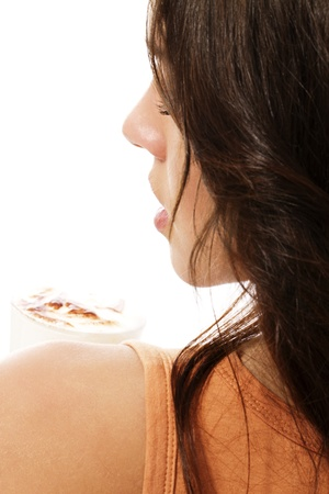 latte macchiato: looking over the shoulder of a beautiful woman with latte macchiato coffee on white background