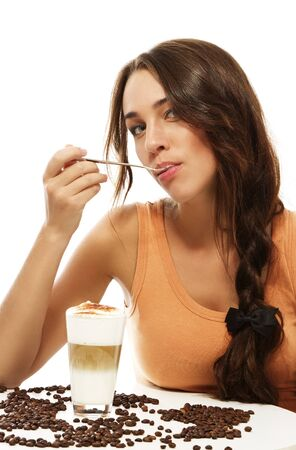 young woman with spoon in her mouth sitting at a table wit latte macchiato coffee on white background Stock Photo - 12630317