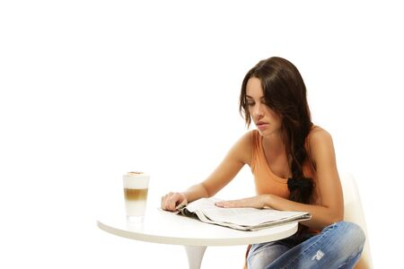young woman reading newspaper at a table with latte macchiato coffee on white background