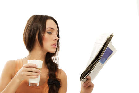 young woman reading newspaper holding latte macchiato coffee on white background photo