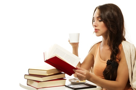 e book: beautiful woman drinking coffee while reading book on white background Stock Photo