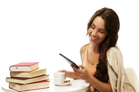 happy young woman reading ebook near books on white background photo