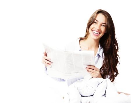 leggere rivista: donna felice a letto con un giornale su sfondo bianco