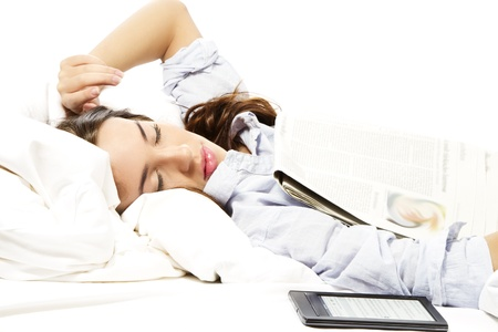 sleeping tablets: woman felt asleep under a newspaper with ebook reader aside on white background