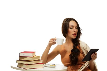 beautiful woman holding coffee reading ebook on white background Stock Photo