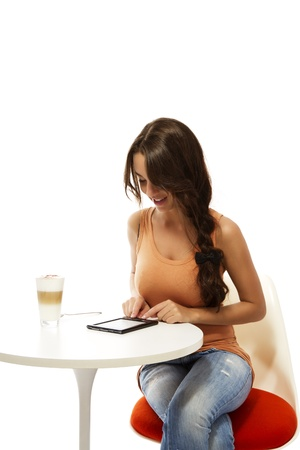 beautiful woman at a table with latte macchiato reading ebook on white background photo