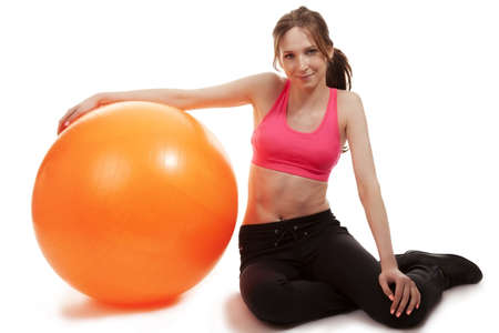 with orange and white body: young sporty woman with a fitness ball on white background