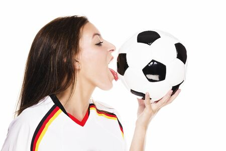 beautiful woman wearing football shirt licking on a football on white background photo