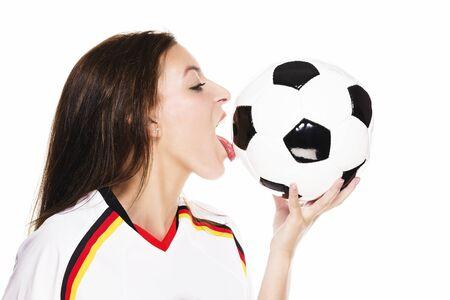 soccer wm: mujer hermosa que desgasta lamiendo Camiseta de f�tbol en un bal�n en el fondo blanco
