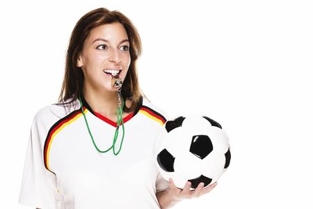 soccer wm: beautiful woman wearing football shirt with a whistle holding football on white background