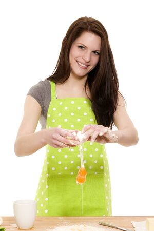 young beautiful woman adding egg to flour on white background photo