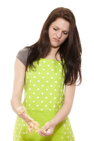 young beautiful woman cleaning her hands from dough on white background photo