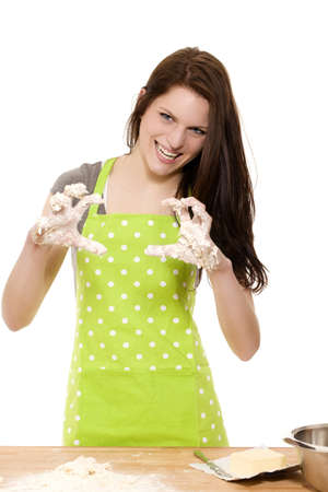 young woman at baking forming claws with her messy dough covered hands on white background photo