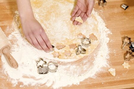 closeup of hands pressing christmas molds in dough on a kitchen table Stock Photo - 14031372