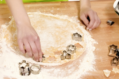 closeup of hands pressing christmas molds in dough on a kitchen table photo