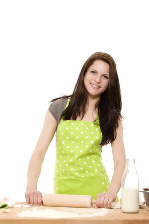 happy woman baking using rolling pin on dough on white background photo