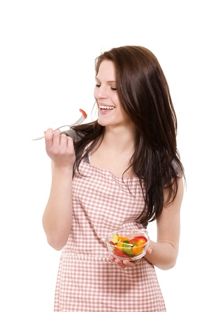 happy young woman with red apron eating salad on white background photo