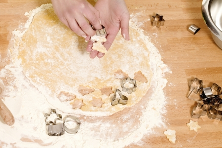 closeup of hands holding christmas formed dough for baking photo