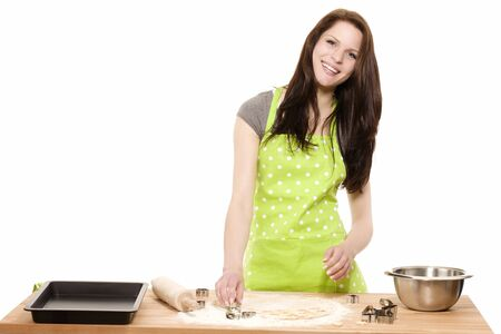 happy young woman pressing christmas molds in dough with white background photo