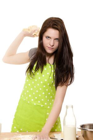 serious looking woman about to throwing dough in front of white background photo