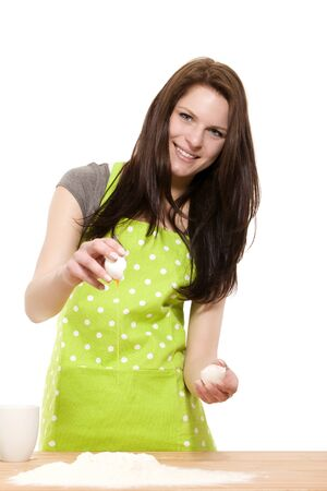 happy young woman adding an egg to flour for baking on white background photo