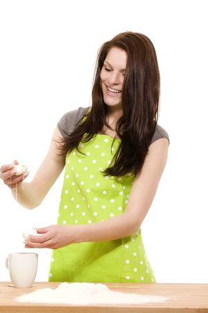 yolk: young happy woman preparing eggs for  baking with flour on white background Stock Photo