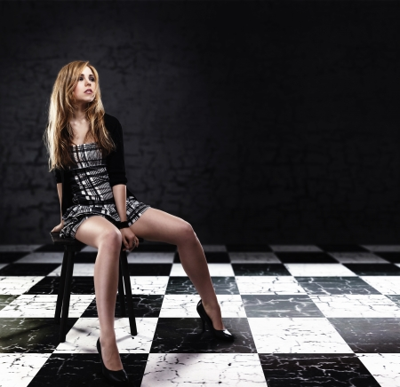 young woman in checked skirt sitting on a stool on checked floor with grey background photo