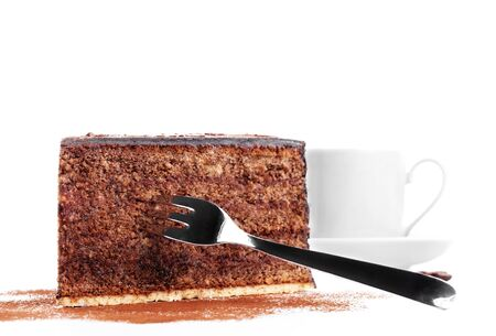 chocolate cake with a fork and a cup of coffee in background on white background photo