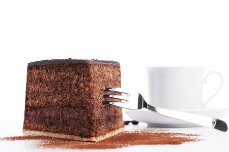 chocolate cake with a fork and a cup of coffee in background on white background Stock Photo - 14193320