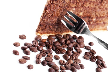 chocolate cake with a fork inside and coffee beans on white background photo