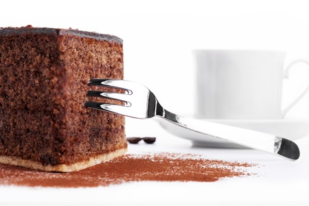 closeup of a chocolate cake with a fork and a cup of coffee in background on white background photo