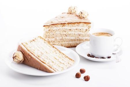 avellanas: pastel de crema de avellana con una taza de café y tres avellanas en el fondo blanco