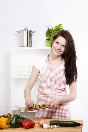 happy woman in kitchen adding cutted cucumber to her salad photo