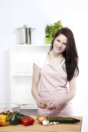 happy woman preparing cucumber for her salad photo
