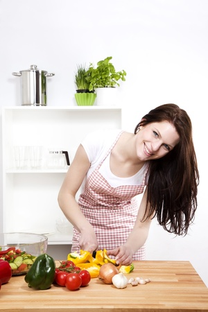 happy woman in a kitchen cutting yellow paprika for salad photo