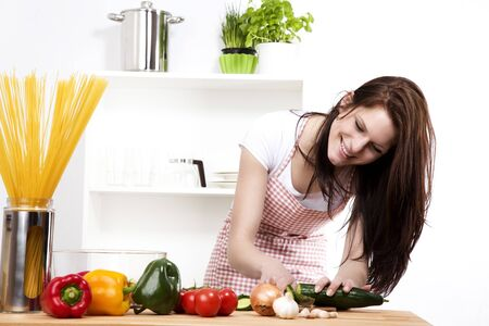happy woman in kitchen chopping cucumber photo