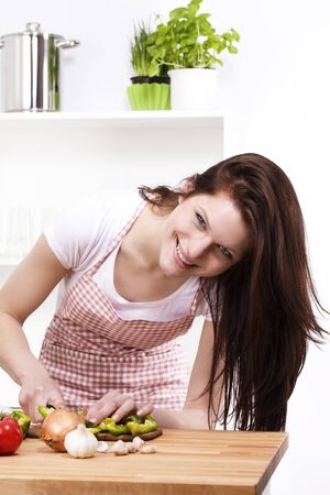 happy young woman in kitchen cutting paprika photo