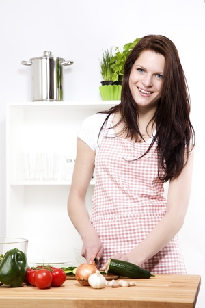chopping: happy young woman in a kitchen cutting cucumber for salad Stock Photo