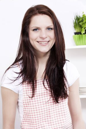 portrait of a happy smiling young woman in kitchen photo