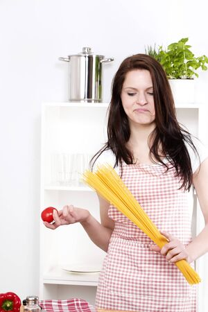 young woman holding pasta and tomato looking at the tomato in her hand photo